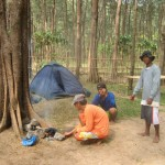 3 men close to a small bonfire in the forest; 2 tents farther
